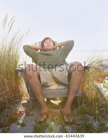 Young man sleeping in chair at beach - stock photo
