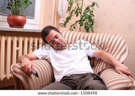 Young man sleeping in front of TV set - stock photo