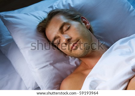 Young Man Sleeping in his Bed - stock photo