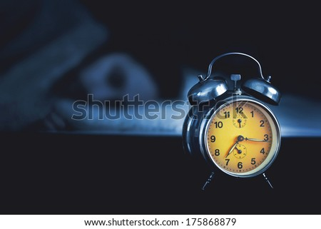 Young man sleeping in the bed. It is quarter past seven in the morning. - stock photo