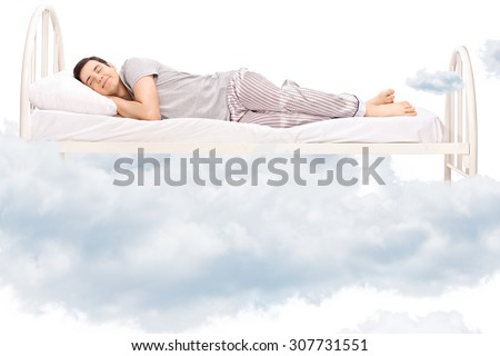 Young man sleeping on a comfortable bed in clouds isolated on white - stock photo