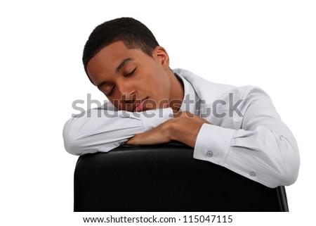 Young man sleeping on the job - stock photo