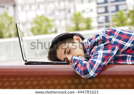 young man sleeping on the laptop - stock photo