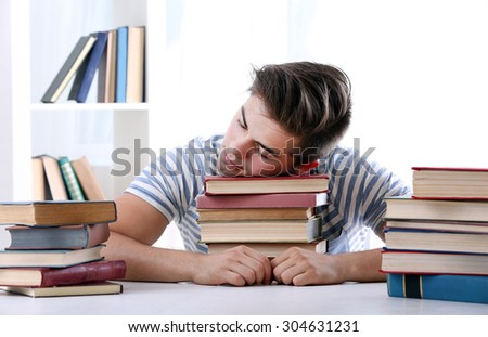 Young man sleeping with books at table in room - stock photo