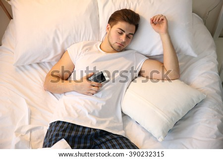 Young man sleeping with mobile phone in bed at home - stock photo