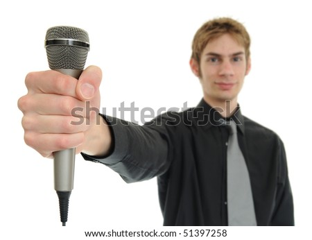 Young man smiles and holds up microphone on white - stock photo
