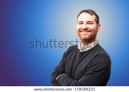 Young man smiling against blue background.