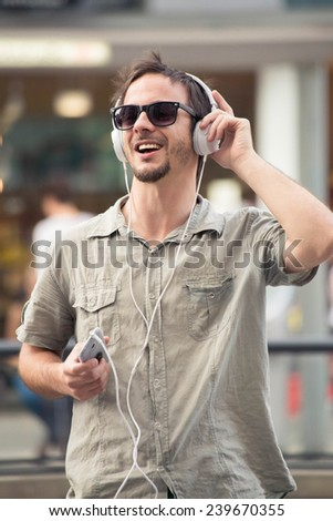 Young man smiling and enjoying music on smart-phone  - stock photo
