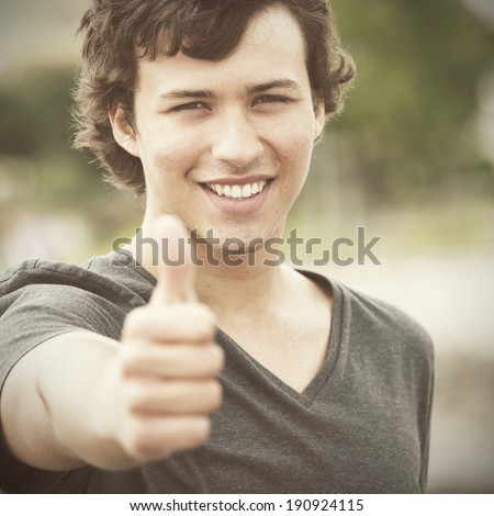 young man smiling and gesturing OK - stock photo