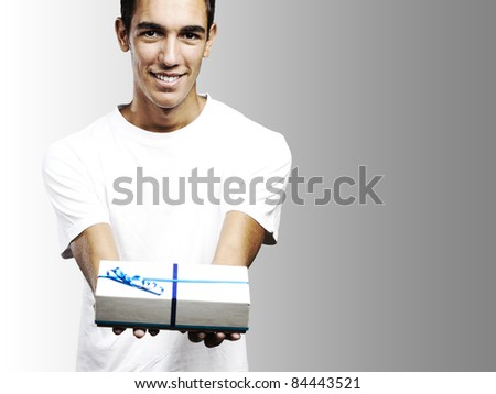 young man smiling and giving a gift against a grey background - stock photo