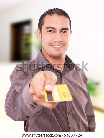 Young man smiling and giving his credit card - stock photo