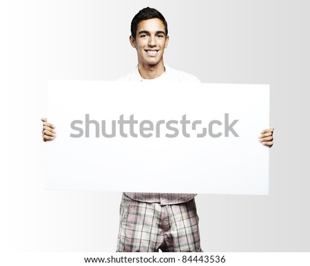 young man smiling and showing a big banner against a grey background - stock photo