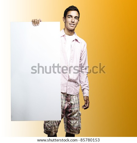 young man smiling and showing a big banner against a yellow background - stock photo