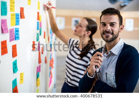 Young man smiling at camera while colleague writing on white board in the background - stock photo
