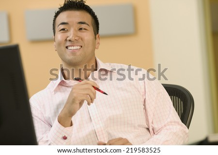 Young man smiling at his desk - stock photo