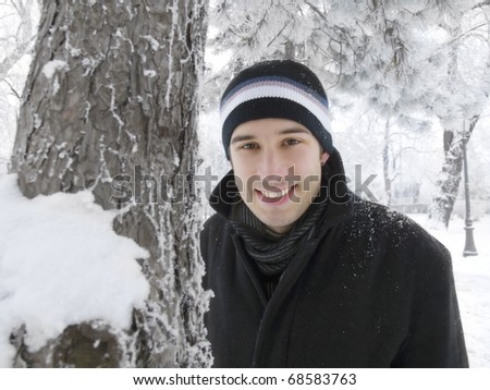 young man smiling in winter park - stock photo