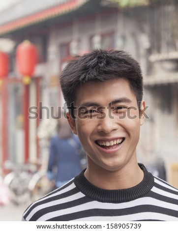 Young man smiling looking at camera - stock photo