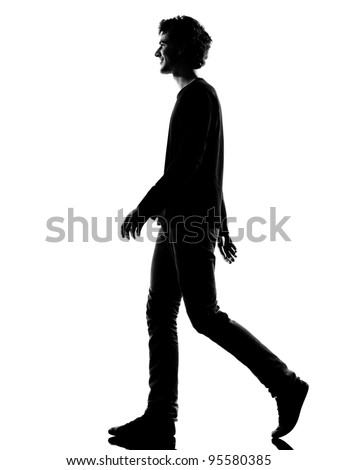 young man smiling walking silhouette in studio isolated on white background