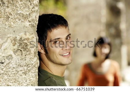 Young man smiling while waiting for his girlfriend - stock photo