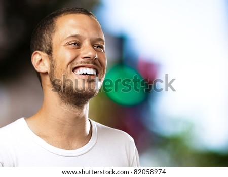 young man smiling with a city as a background - stock photo