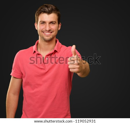 young man smiling with thumbs up isolated on black background