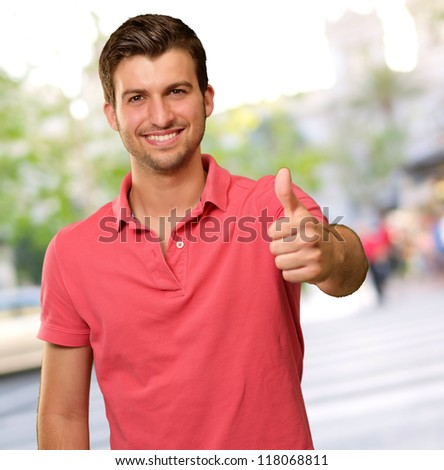 young man smiling with thumbs up, outdoor - stock photo