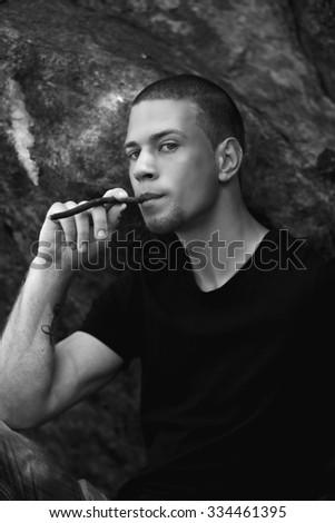 young man smokes a cigar - stock photo
