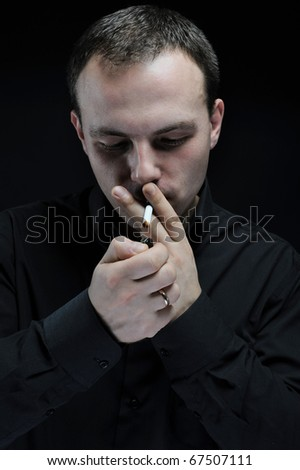 young man smokes a cigarette on a dark background - stock photo