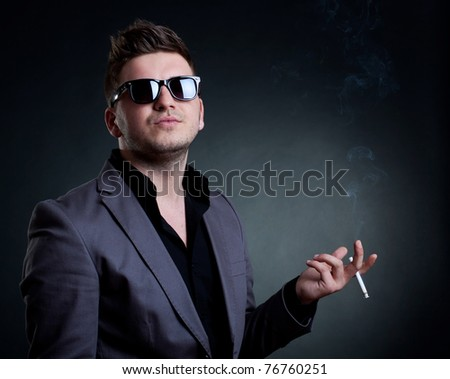 young man smoking a cigarette and having a superior attitude