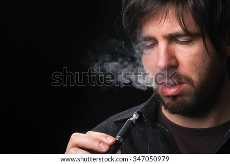 Young man smoking electronic cigarette on black background