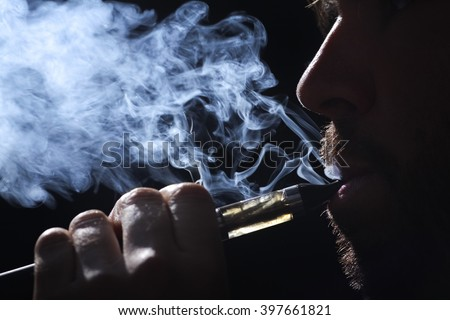 Young man smoking electronic cigarette on black background - stock photo