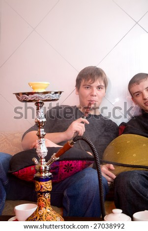 young man smoking hookah in the room - stock photo