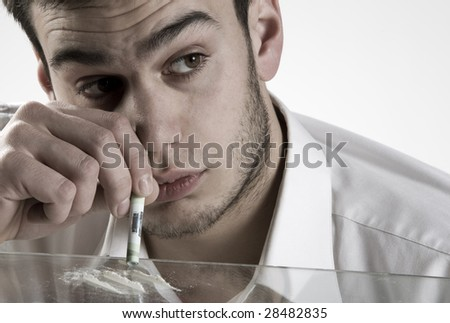 Young man sniffing cocaine. - stock photo