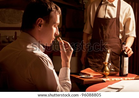 Young man sniffing the cork of a wine bottle - stock photo
