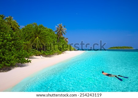 Young man snorkeling in tropical island with sandy beach, palm trees and turquoise clear water - stock photo