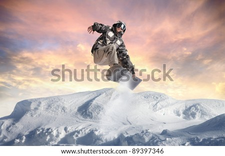 Young man snowboarding in the mountains - stock photo