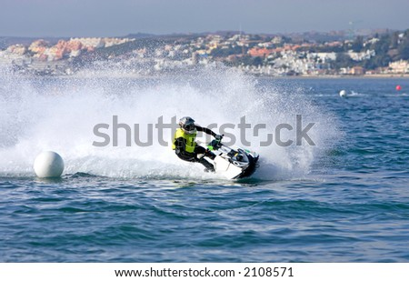 Young man speeding towards a marker buoy on a small jetbike or jetski during a race on the sea or ocean