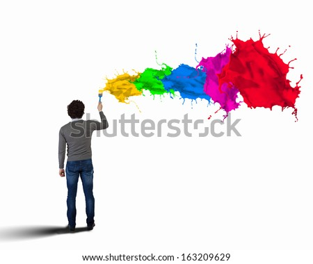 Young man spraying colour paints over background