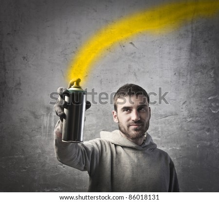 Young man spraying yellow paint - stock photo