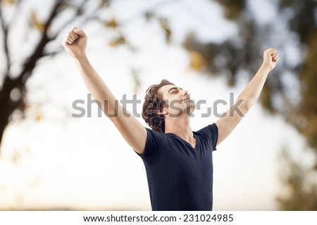 Young man spreading arms in nature - stock photo