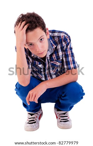 young man squatting, worried, isolated on white background studio shot - stock photo