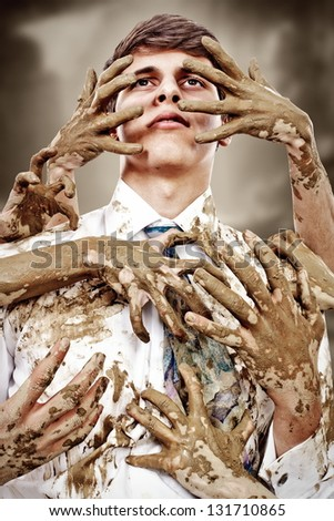 Young man stained by multitude of dirty hands - stock photo