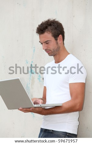 Young man standing against a wall with laptop computer - stock photo