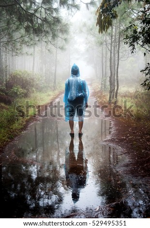 Young Man standing alone a hillside with their hands up in forest outdoor with nature on background Travel Lifestyle and survival concept