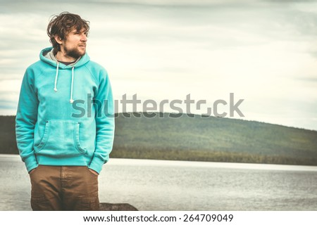 Young Man standing alone outdoor with scandinavian mountains and lake on background Lifestyle and melancholy emotions concept - stock photo