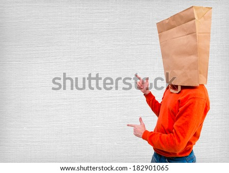 Young man standing and gesturing with ecological paper bag on head - stock photo