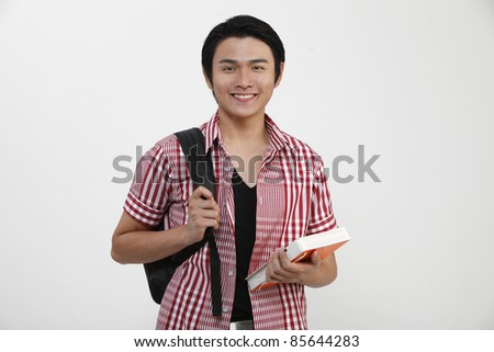 Young man standing and holding books - stock photo
