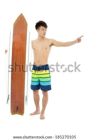 young man standing and point forward with surfboard - stock photo