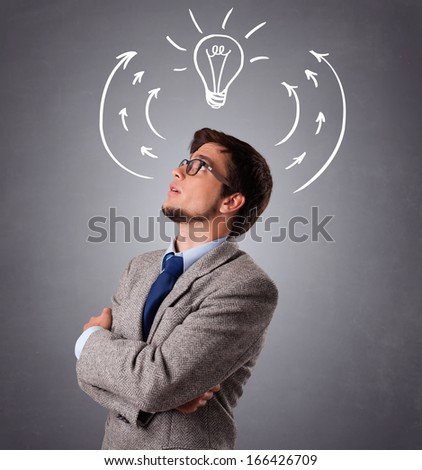Young man standing and thinking with arrows and light bulb overhead - stock photo