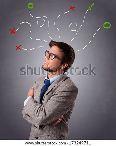 Young man standing and thinking with marks overhead - stock photo